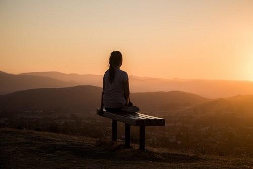 femme qui médite sur un banc face à un paysage
