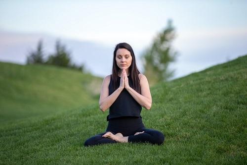 femme qui se déstresse en méditant sur une prairie