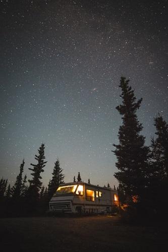 camping-car au milieu de la nuit et au milieu des arbres en pleine nature